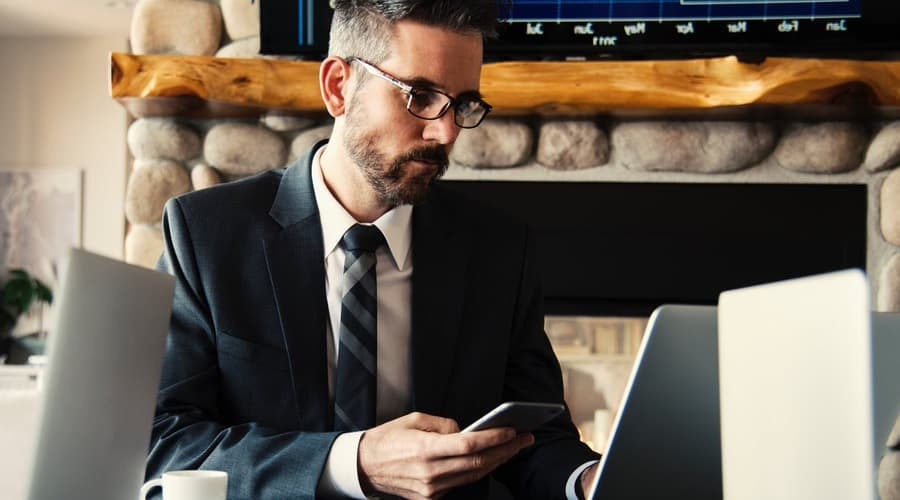 The picture shows a man that is working with his mobile in the hand and his laptop on the desk. he wears glasses. Those situations are optimally for the Shamir Autograph Intelligence.