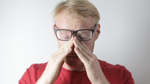 this picture shows a man with his glasses rubbing his eyes